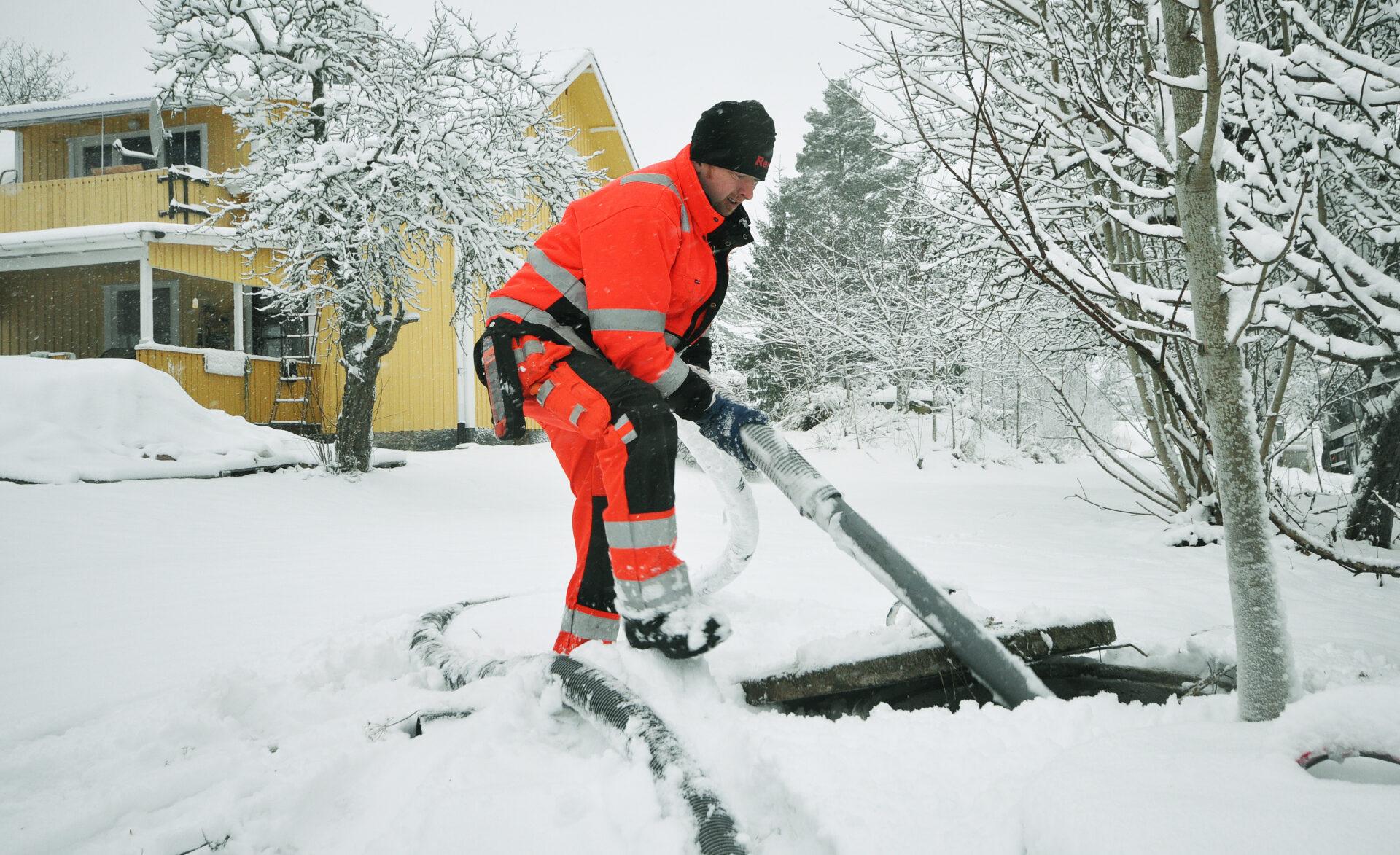 Arbetare spolar avlopp utanför bostad. Avloppsspolning får bort avlagringar, slam och grus ur rör och ledningar.