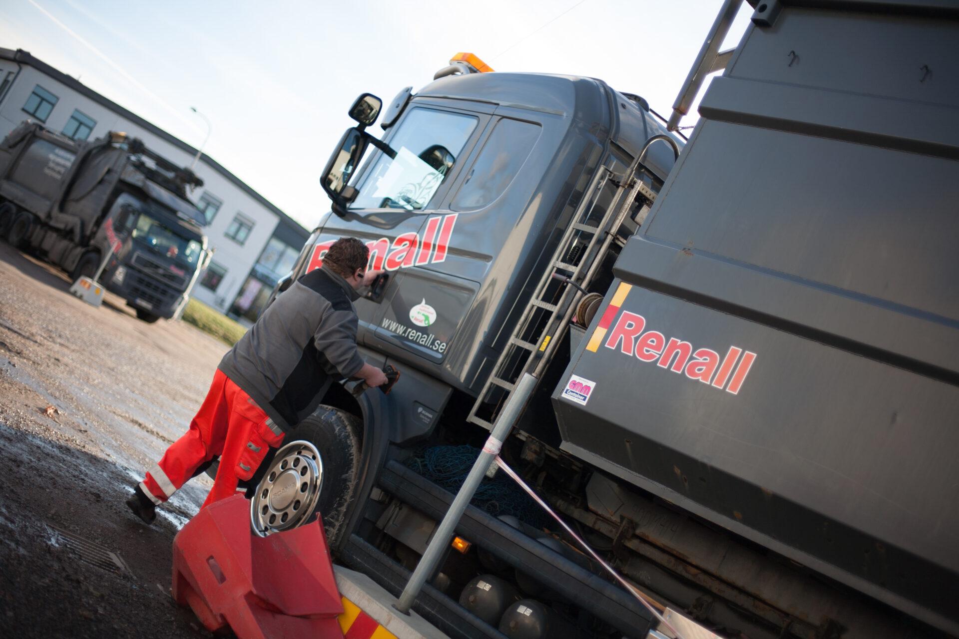 Person påväg att öppna dörren till en av Renalls lastbilar.